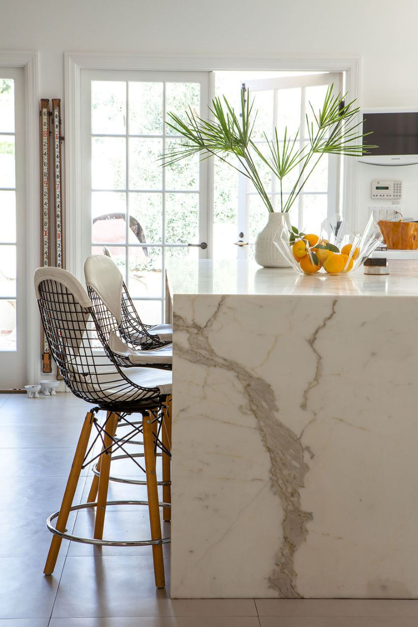 Oranges and tropical greenery in a kitchen with marble details