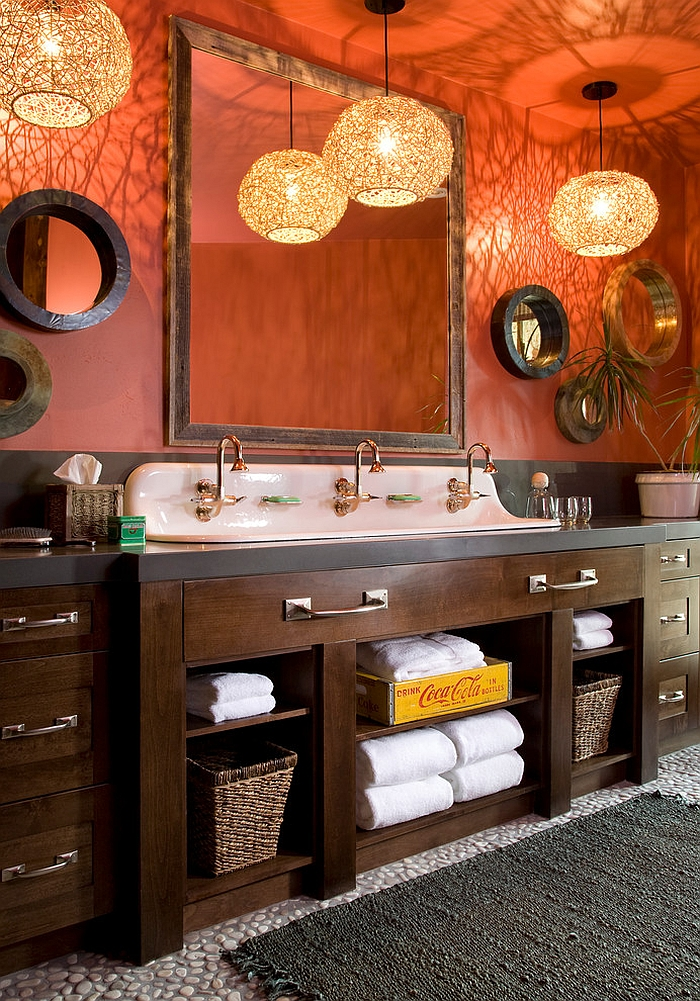 Pendant lights elevate the appeal of the rustic bathroom in orange [Design: Studio 80 Interior Design]