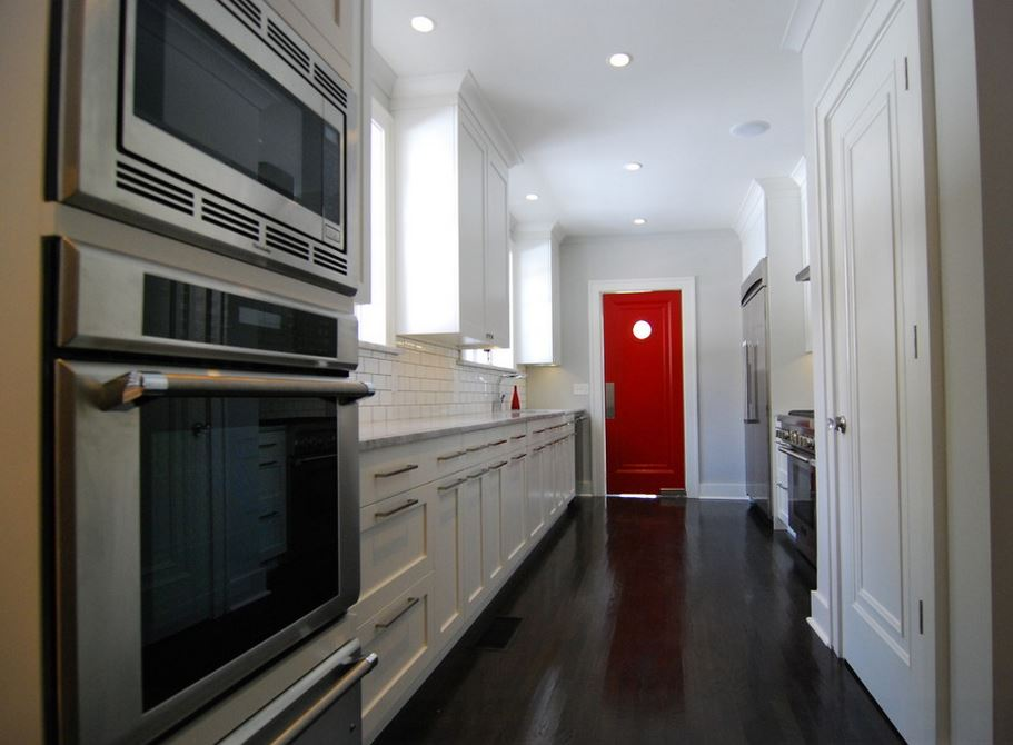 Red door in a white kitchen with dark flooring