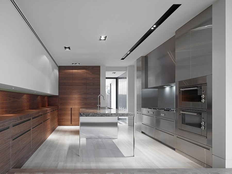 Reflective surfaces and wooden counters add textural contrast to the sleek kitchen
