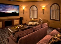 Round tufted walls and lovely lighting give the home theater a cozy, warm vibe
