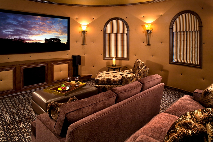 Round tufted walls and lovely lighting give the home theater a cozy, warm vibe [Design: VM Concept Interior Design Studio]