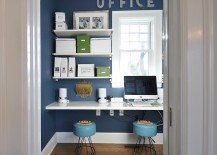 Small home office design with sleek shelves in white and a blue backdrop