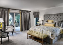 Tufted headboard and silken drapes give the room an air of luxury