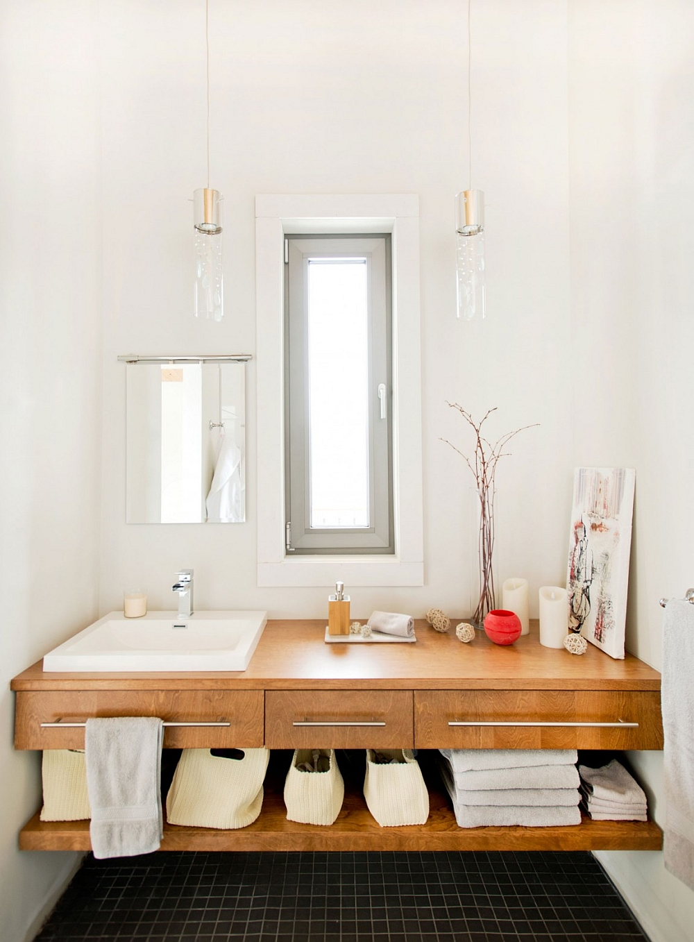 White bathroom with black floor tiles and wooden vanity