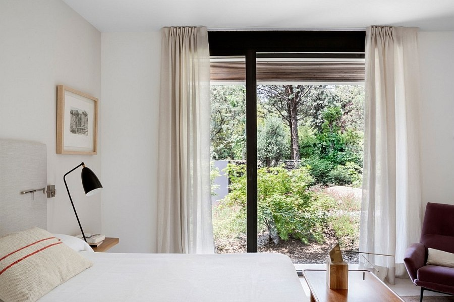 White sheer curtains improve the insulation of the bedroom even while letting in naural light