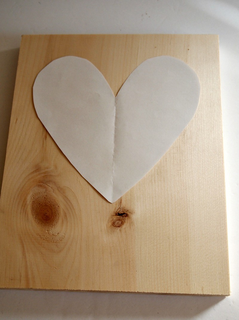 Place the heart template on the sheet of pine