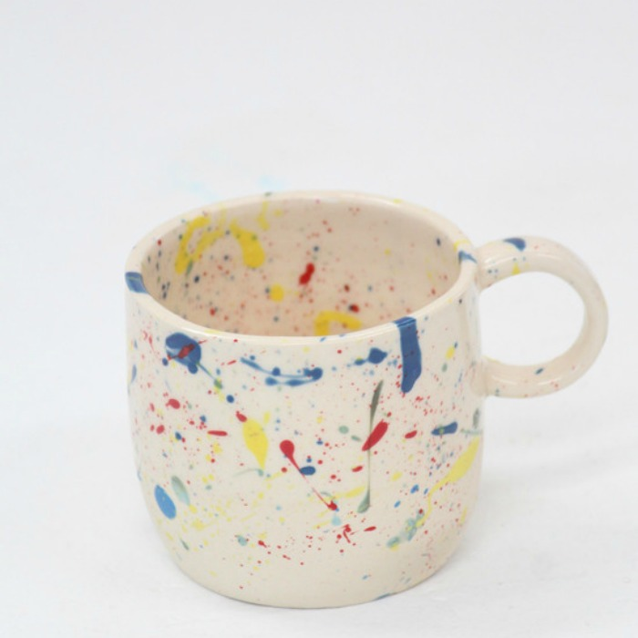 The splatter mug is hand painted in New York