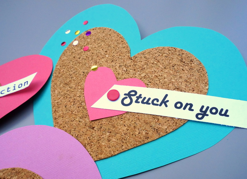 Confetti and thumbtacks decorate a valentine