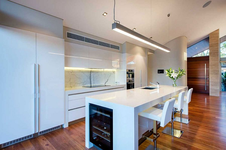 Contemporary kitchen in white with smart island and marble backsplash