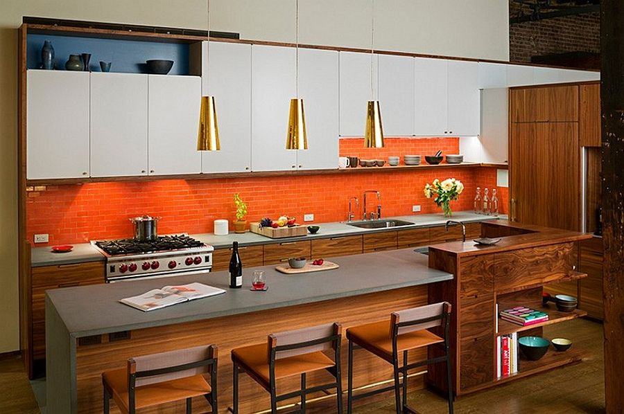 Orange backsplash and bold metallic pendants breathe life into the kitchen