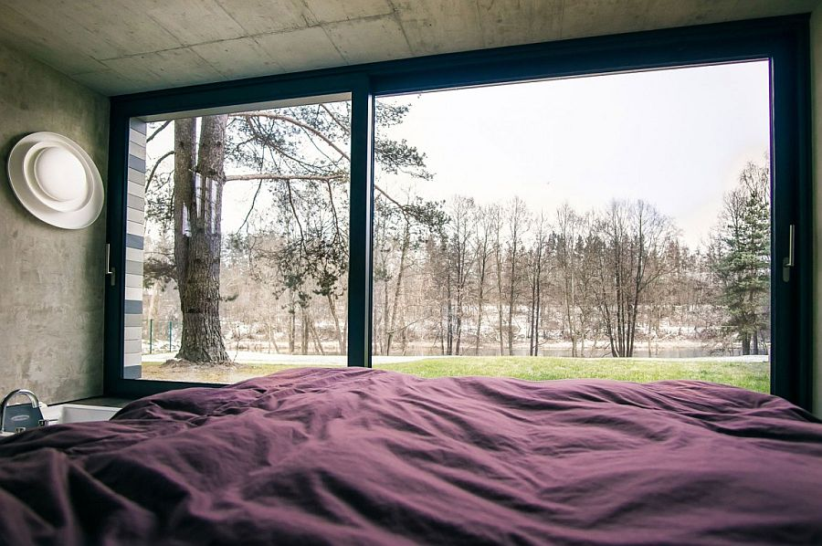 Plush bedroom of the home with concrete walls and lovely forest view