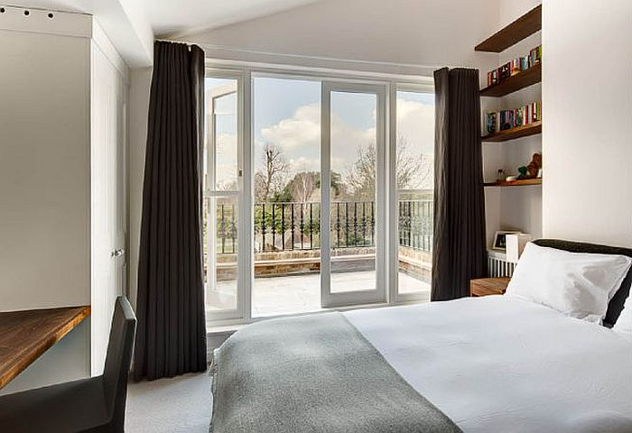 Plush bedroom with private balcony and view of the rear garden