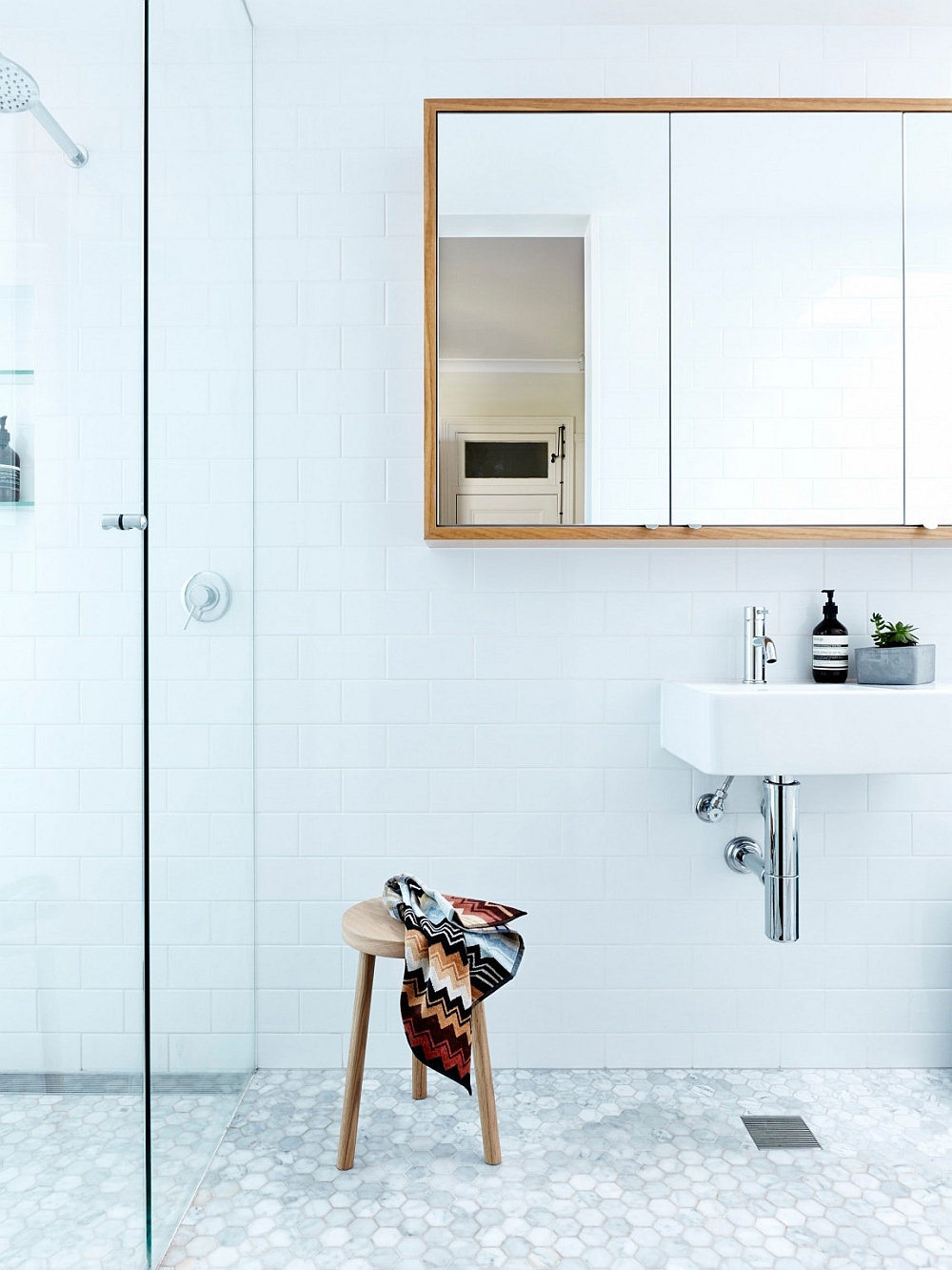 Simple wooden accents bring class and warmth to the contemporary bathroom