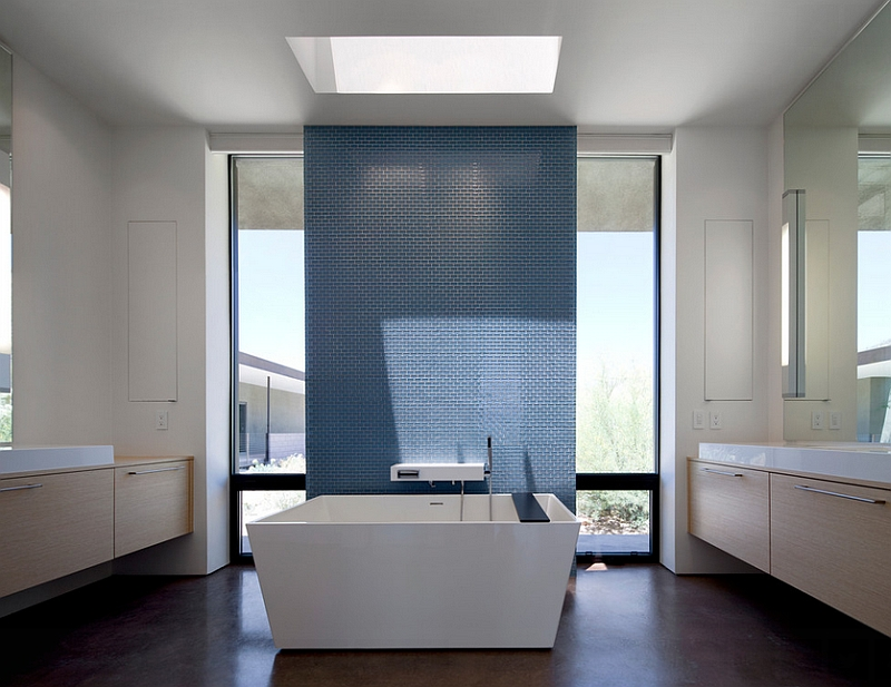 Skylight sheds the spotlight on the accent wall in the minimalist bathroom [Design: Ibarra Rosano Design Architects]