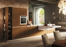 Walnut wooden storage units combine with sleek Corian suspended worktop in the kitchen