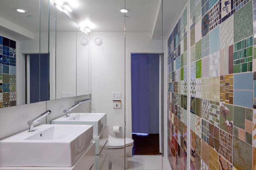 A mirrored wall in a bathroom with colorful tile