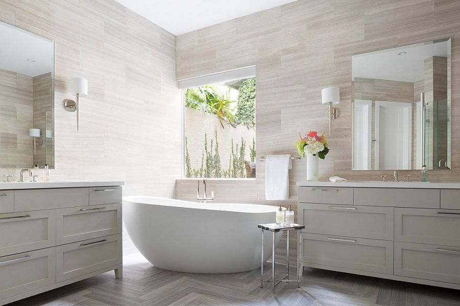 Bathroom with gray vanity units and a standalone bathtub in white