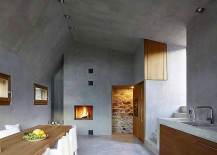 Beautiful fireplace and concrete walls shape the minimal setting
