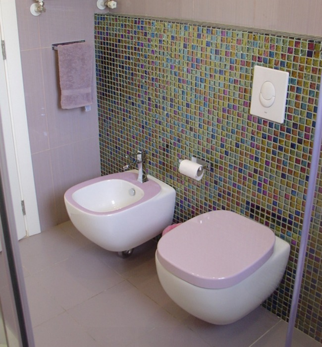 A lavender and white bidet and matching toilet