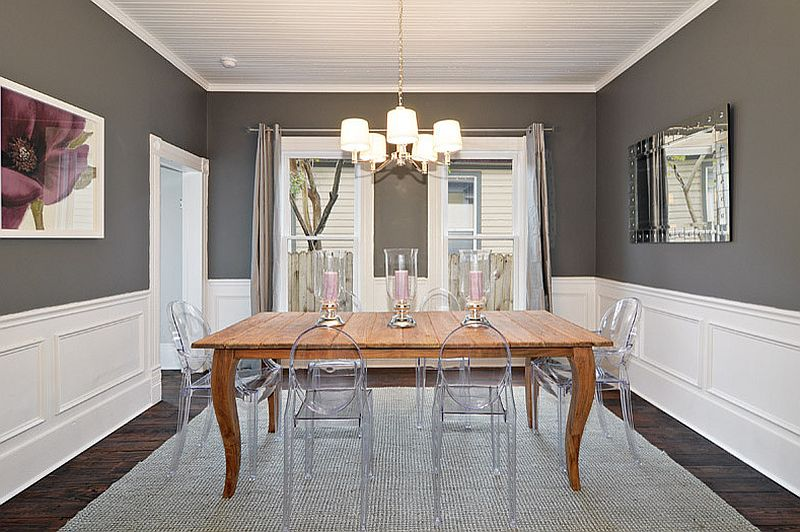 Lovely charcoal gray dining room with acrylic chairs and wooden table [Design: Avenue B Development]
