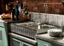 Lovely metal backsplash and brick walls in the vintage kitchen