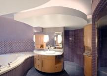 Sensational purple tiles and custom vanity shape the stunning bathroom
