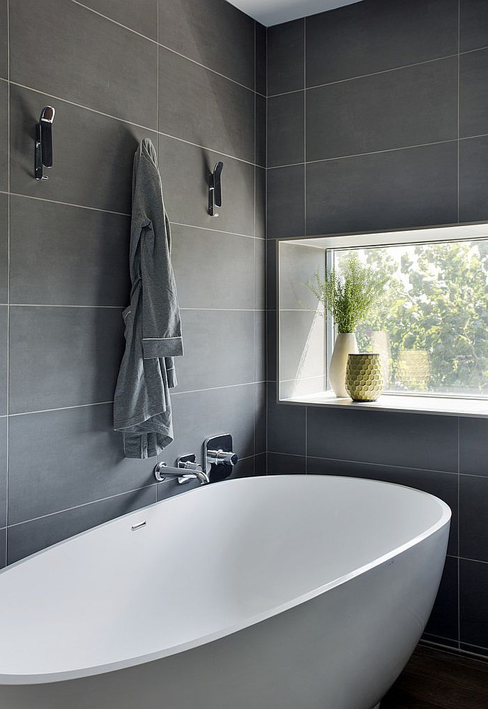 Standalone bathtub in white in a bathroom with gray wall tiles