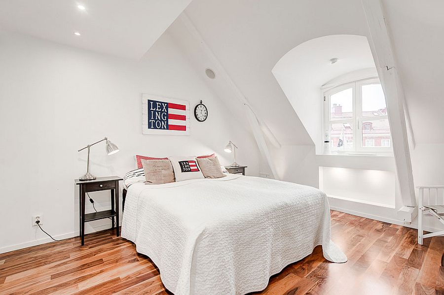 Stylish Scandinavian style attic bedroom in white with wooden flooring