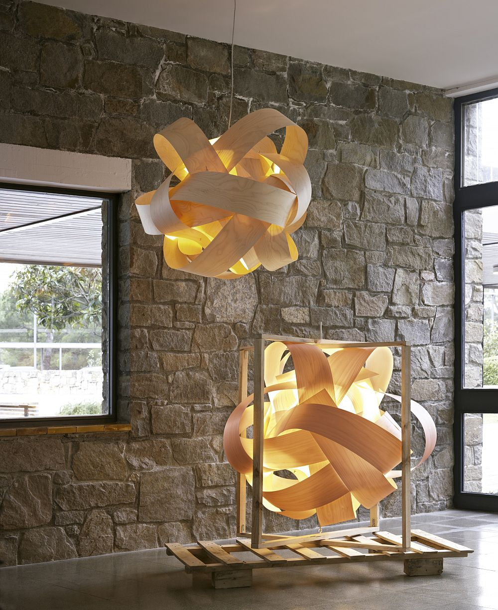 Thin slats of birch wood knotted around stainless steel frame shape the stunning pendant