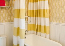 Wallpaper and shower curtains bring yellow to the small bathroom