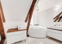 Wooden beams of the attic apartment add a unique visual to the soothing bathroom in white