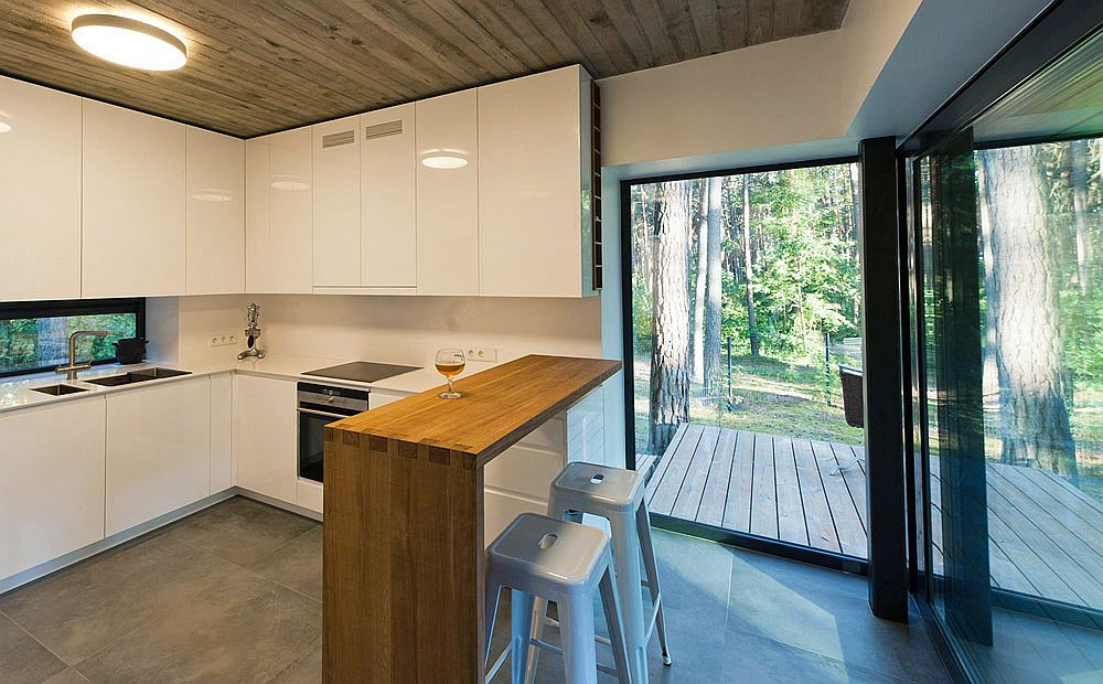 All white kitchen with a wooden serving area and breakfast zone