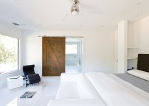 All white minimal bedroom with a lovely barn door for the bath