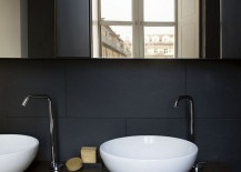 Black backdrop and white sinks along with a wooden vanity in the bathroom