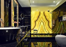 Brilliantly backlit onyx in the bathroom adds gold to the dark space