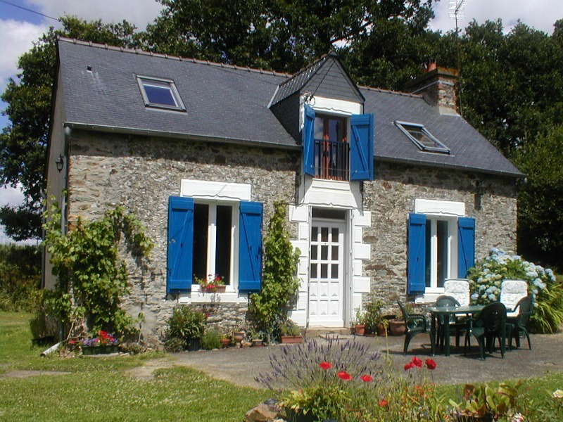 The bright blue shutters help make this cottage seem fresh and modern