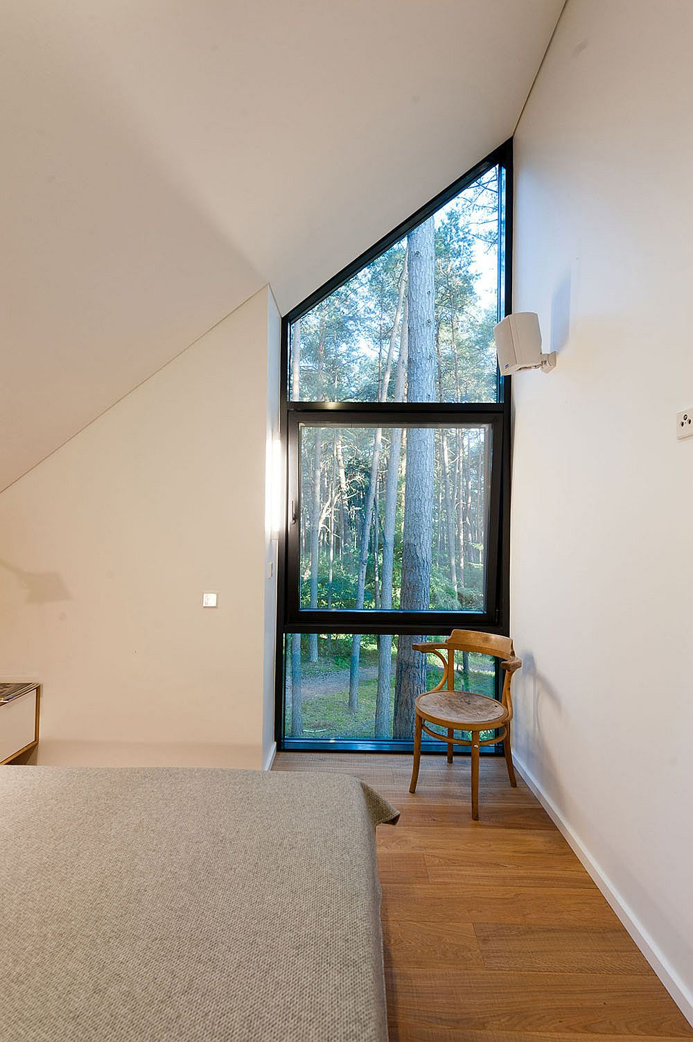 Corner window in the bedroom offers a view of the lush green outdoors