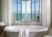 Elegant chandelier and vintage bathtub shape a dreamy bathroom