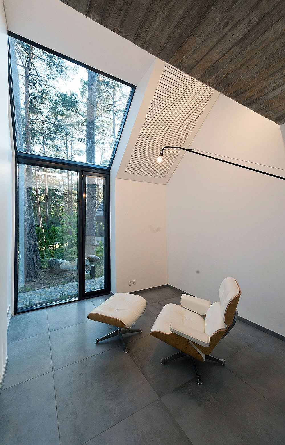 Iconic Eames Lounger sits inside the Black House Blues overlooking the forest
