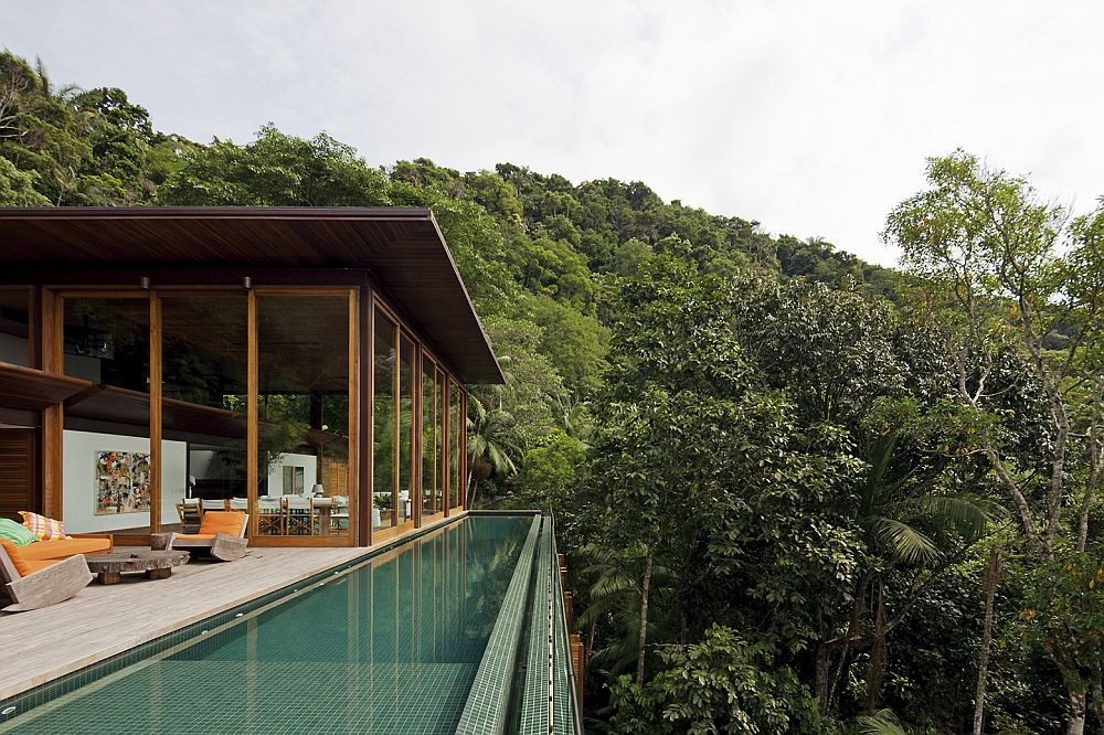 Lavish pool area of the gorgeous Brazilian home with lush green canopy around