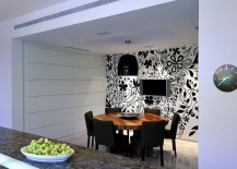 Lighting adds to the appeal of the striking black and white wallpapere in the dining room