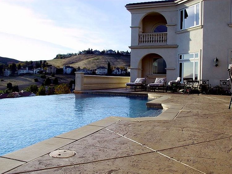 Mediterranean style pool area with stamped concrete deck [Design: Christopher Lines & Associates]