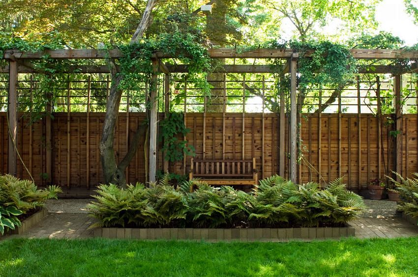 Modern pergola with seating and a gravel path