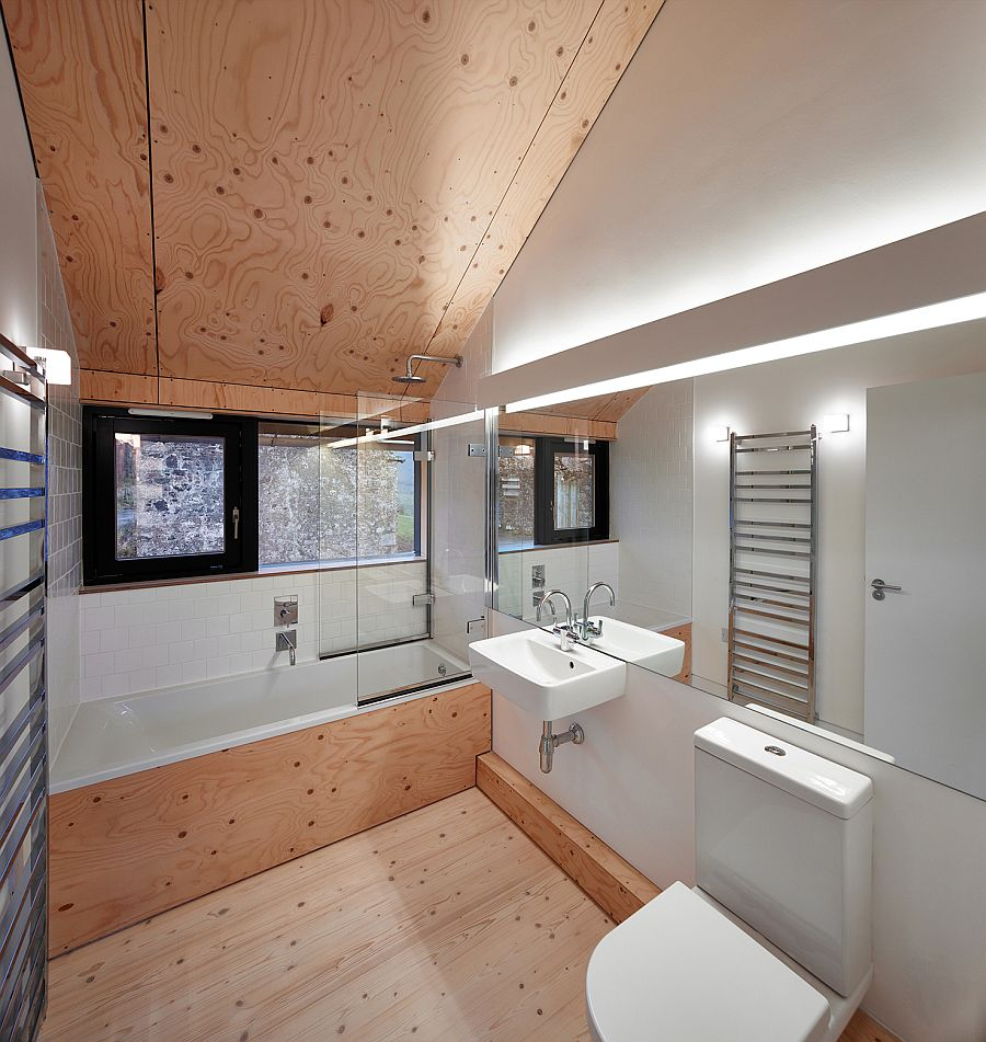 Neutral color scheme and slanted wooden ceiling inside the modern bath