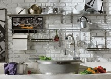 Open stainless steel shelves set against brick wall in the kitchen