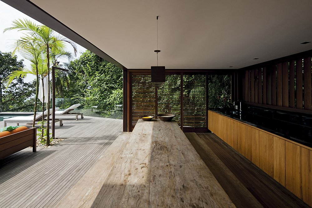 Outdoor kitchen and dining space that opens up towards the private deck
