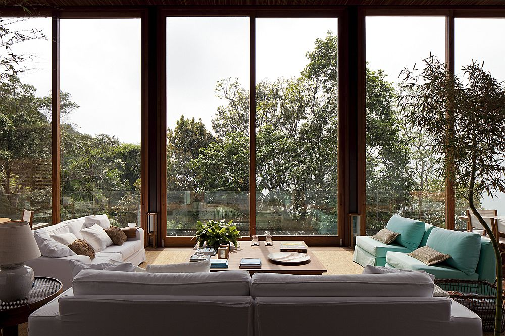 Outdoor sitting area in a glass enclosure with a view of the forest and the ocean