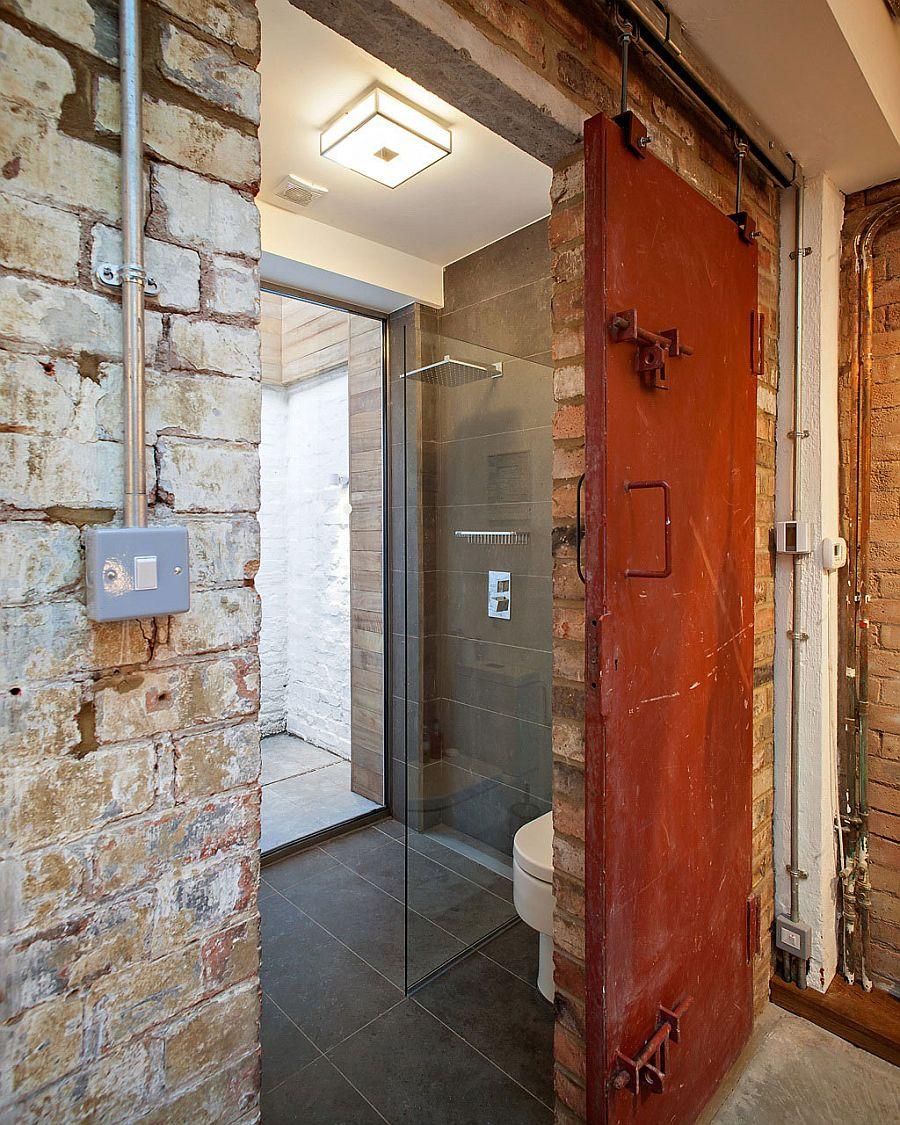 Sliding metal door and brick walls shape the small bathroom