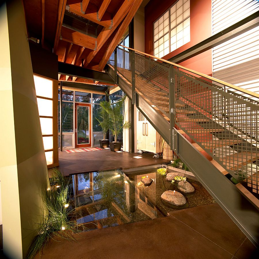 Small indoor water feature with a glass walkway and a staircase above [Design: Kevin Akey -AZD Architects]